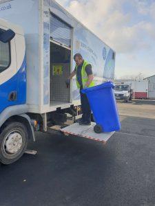 Lifting a shredding bin on to the truck