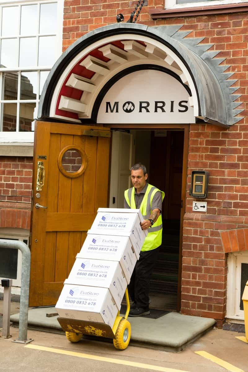 Kane leaving Morris & Co. with their storage boxes