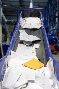 Paper going up the shredding conveyor ready to be shredded
